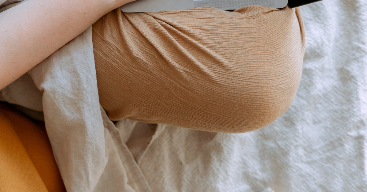 A close up of a person sitting on a bed